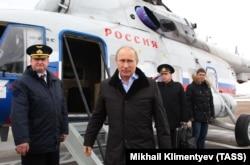 Путин выходит из вертолета на авиабазе Крымск на юге России в январе 2013 года. На заднем плане офицер с ядерным чемоданчиком отдает честь