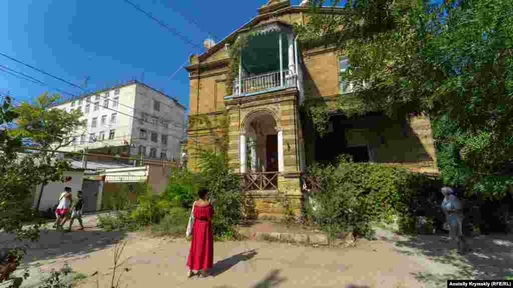 Дівчина фотографує на смартфон старовинний будинок з черепашника на вулиці Дувановської