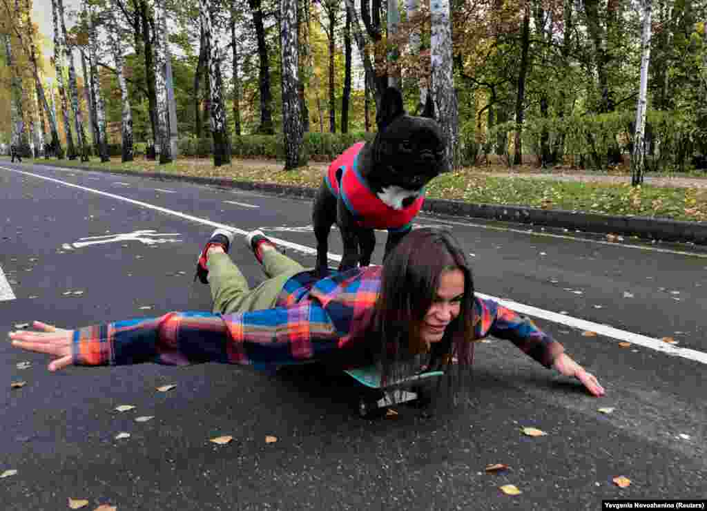 A French bulldog named Nord Boss stands on the back of his owner, Natasha, while they skateboard in Moscow. (Reuters/Evgenia Novozhenina)