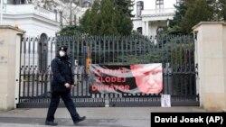 Un polițist trece pe lângă un afiș atașat de protestatari la o poartă a ambasadei ruse la Praga, Republica Cehă, vineri, 16 aprilie 2021.