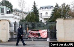 """A Czech policeman outside the Russian Embassy walks past a banner attached by protesters during the diplomatic dispute in April. It shows a picture of Russian President Vladimir Putin with the words: """"Killer, thief, dictator."""""""