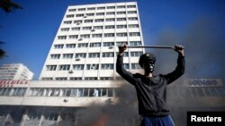 """A protester stands near a fire set in front of a government building in Tuzla, Bosnia-Herzegovina, earlier this year. The Freedom House report describes the Balkan country as the """"poster child"""" of dysfunctional government."""