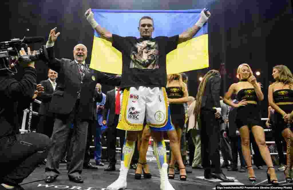 Український боксер Олександр Усик, який завоював титул чемпіона світу за версіями Всесвітньої боксерської ради (WBC), Всесвітньої боксерської організації (WBO), Всесвітньої боксерської асоціації (WBA) і Міжнародної боксерської федерації (IBF) у вазі до 90,71 кілограма в об'єднавчому бою з російським боксером Муратом Гассіевим, у фіналі Всесвітньої боксерської суперсерії WBSS. Москва, 22 липня 2018 року. НА ЦЮ Ж ТЕМУ