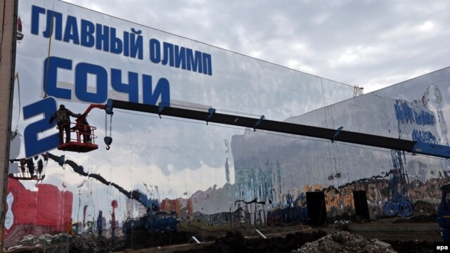 Workers prepare a building of the Olympic Main Store at the Olympic Park in Sochi on January 27, less than two weeks before the Opening Ceremony.