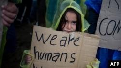 """Иллюстрация. Ребенок-мигрант держит плакат с надписью: """"Мы такие же люди как и ты"""""""