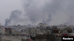 Smoke rises from a Damascus suburb as fighting rages in parts of the Syrian capital on January 29.
