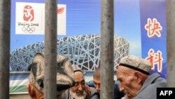 Уйгурские аксакалы сидят под плакатом Пекинской Олимпиады. Кашгар, 6 августа 2008 года.
