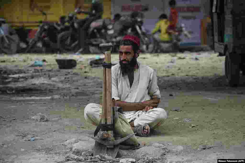 Рабочий сидит у дороги со своими инструментами, ожидая, пока клиенты наймут его на дневную работу в Карачи, Пакистан