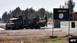 Разрушенный автомобиль на фоне билборда ИГ в сирийской селе близ Ракки.