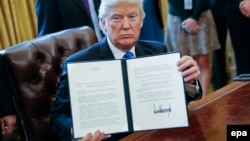 U.S. President Donald Trump holds up one of his recently signed executive orders.