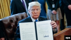 U.S. President Donald Trump displays one of five executive orders he signed in the oval office of the White House in Washington on January 24.
