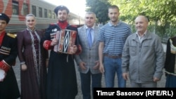 Eugen Martens (second from right) was greeted at the Stavropol railway station by Vladimir Poluboyarenko (right) and his lawyer, Aleksei Abazov, and an amateur musical group that performed a Cossack song and dance.