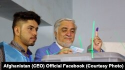 Abdullah Abdullah (L) casts his vote in a polling center in Kabul on September 28.