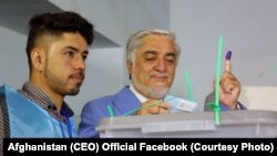 Candidate Abdullah Abdullah casts his vote in a voting center in Kabul. Both candidates immediately declared victory.