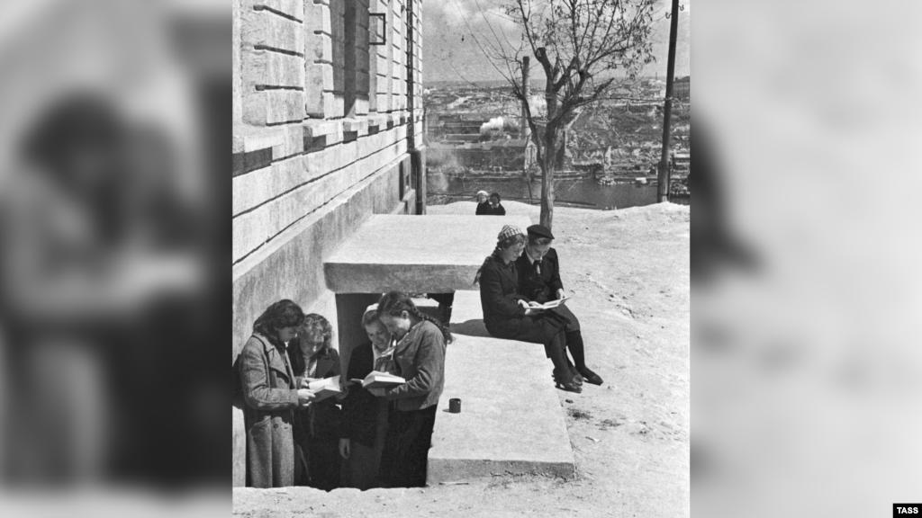 Несмотря на осадное положение, обычная жизнь в городе продолжалась. Учебный процесс – в том числе. Лишь во время немецкого авианалета или артобстрела ученики с книжками перебирались ко входу в бомбоубежище, оборудованного в подвале школы. На фото: ученики у входа в бомбоубежище под школой в Севастополе, апрель 1942 года