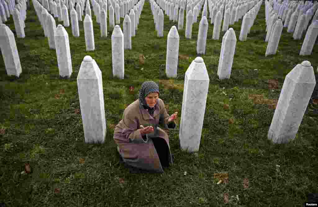 Bida Smajlovic prays near the graves of her husband and brother in Potocari, near Srebrenica, before watching the war-crimes trial of former Bosnian Serb leader Radovan Karadzic in The Hague. Bida lost her husband and brother and dozens of other members of her family in the war. (Reuters/Dado Ruvic)