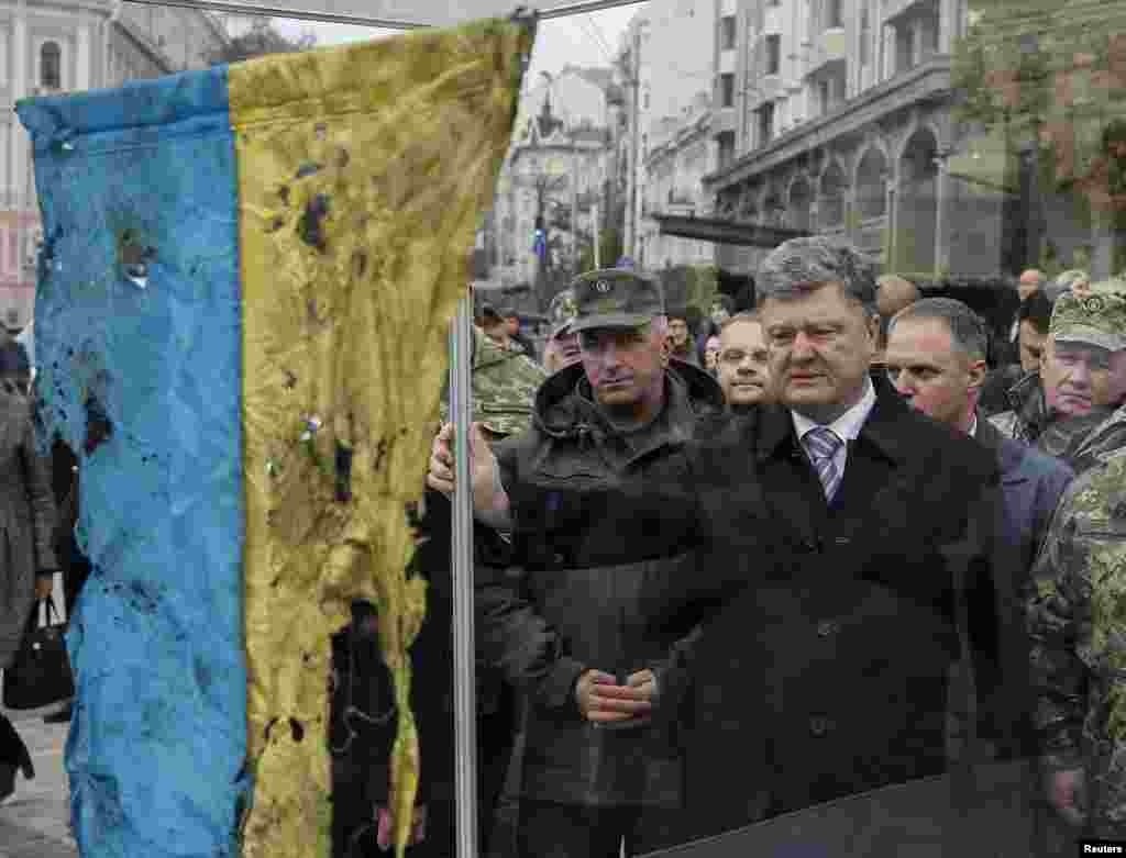 Ukrainian President Petro Poroshenko (center) looks at a Ukrainian flag retrieved from the bloody retreat from Ilovaisk in eastern Ukraine in late August 2014. The country marks Defenders Day on October 14. (Reuters/Gleb Garanich)