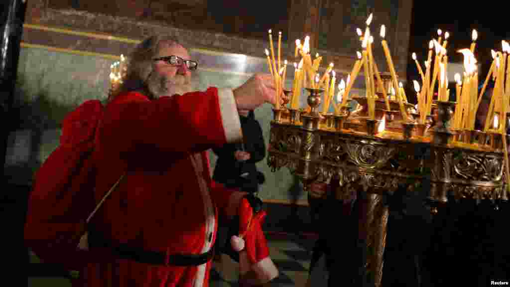 БУГАРИЈА - Маж облечен како Дедо Мраз пали свеќа во катедралата Александар Невски во Софија. Бугарија е членката на ЕУ која го презема нејзиното претседателствување за оваа година. Бугарија, која се приклучи на ЕУ во 2007 година, се очекува да ги зголеми шансите на своите соседи од Западен Балкан да се приклучат на блокот. Лидерите на ЕУ треба да се состанат со аспиранти од регионот на самитот на 17-ти мај.
