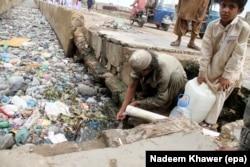 Люди набирают воду для питья и домашних надобностей прямо из свинцовой трубы, выходящей в сточную канаву. Хайдарабад, Пакистан, 2019 год