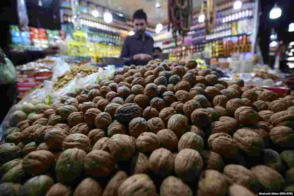 A man sells dried nuts and fruit at his shop in Karachi, Pakistan. (epa-EFE/Shahzaib Akber)
