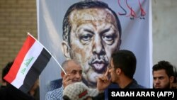 Iraqis stand in front of a banner mocking Turkish President Recep Tayyip Erdogan during a demonstration in Baghdad on October 8 to demand the withdrawal of Turkish troops from the Bashiqa camp in northern Iraq.