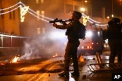 Офицер израильской полиции с направленным на палестинских демонстрантов оружием около Дамасских ворот Старого города в Иерусалиме