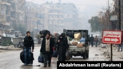 People carry their belongings as they flee deeper into the remaining rebel-held areas of Aleppo, Syria, on December 13.