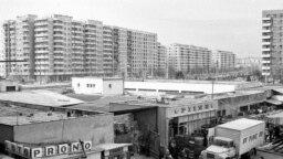"""București, Piața Sălăjan, 1988. Pe după mașina de pâine, lumea face coadă """"să prindă ceva"""" (orice) în timp ce propaganda comunistă se laudă că economia românească se apropie de cea a țărilor avansate. Courtesy: Andrei Bîrsan."""
