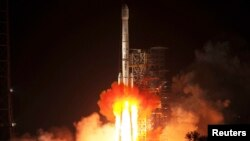 "A rocket, carrying the ""Chang'e-3"" lunar probe, blasts off from a launch pad in China on December 2."