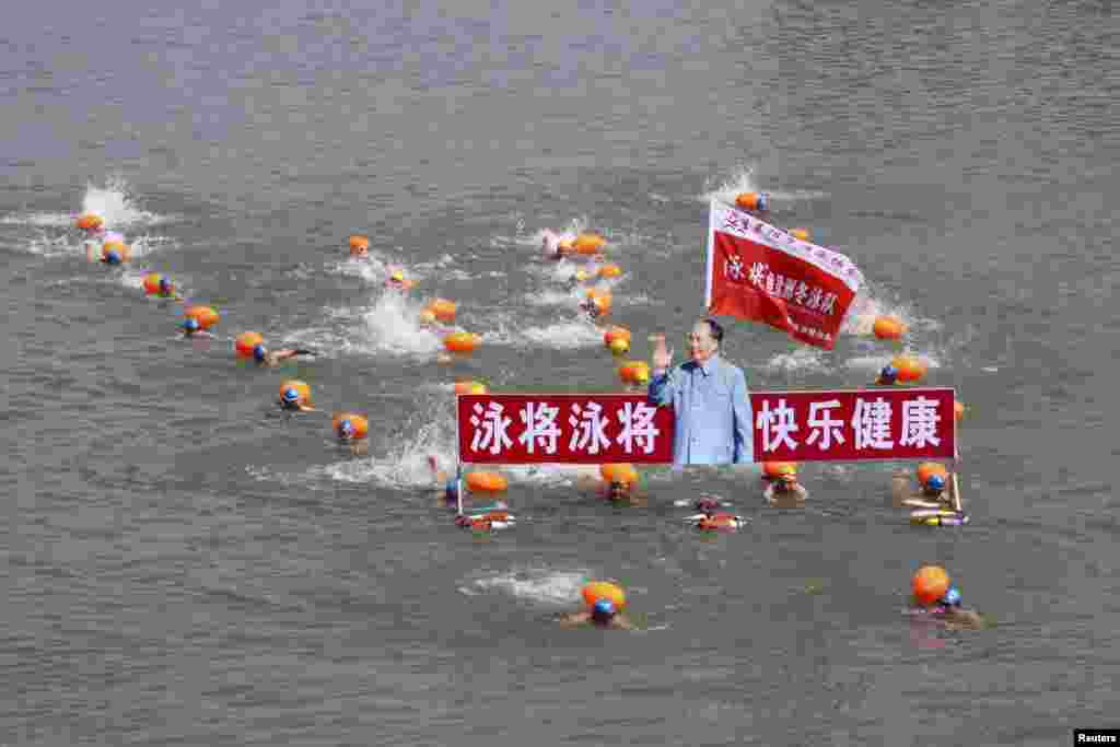 Swimmers carry a portrait of Mao Zedong in the Hanjiang River at a commemorative event for the late Chinese leader in Xiangyang, Hubei province, on July 12. (Reuters)