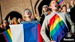 Люди поют российский гимн, держа в руках флаги России и ЛГБТ-сообщества, во время акции протеста против антигейских законов. Стокгольм, 6 октября 2013 года.