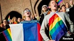 Жыныстық азшылық туын ұстаған адамдар қарсылық акциясында Ресей гимнін айтып тұр. Стокгольм, 6 қазан 2013 жыл.