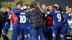 Bosnia-Herzegovina's squad and coaches celebrate qualifying for next year's soccer World Cup after beating Lithuania in October. It will be the first time the Balkan country will be competing at football's blue riband event.