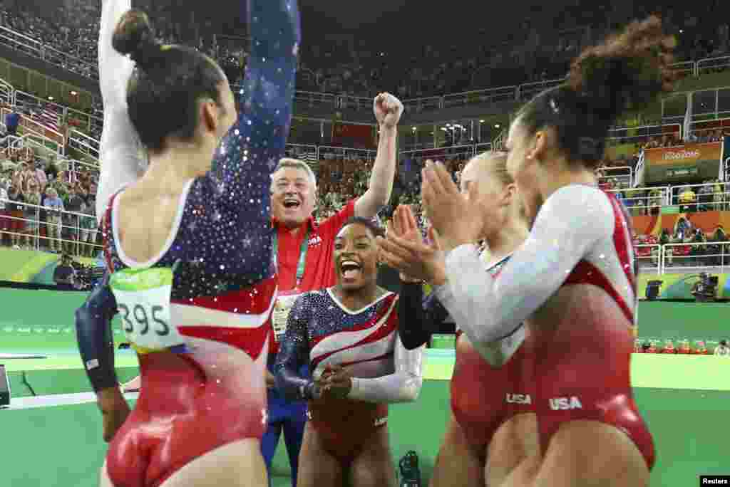 U.S. gymnast Simone Biles (C) celebrates with teammates following her floor routine in the women's team final.