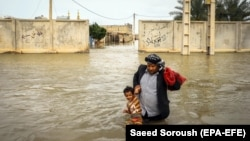 An Iranian man carries his son in a flooded way in a village around the city of Ahvaz, Khuzestan province, March 31, 2019