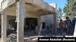 Луѓе ги согледуваат штетите од воздушните напади во област која е под контрола на бунтовниците во градот Алепо.