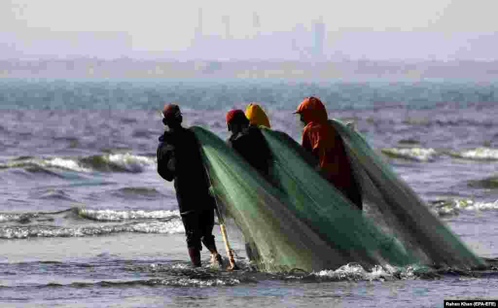 Fishermen carry a net as they go about their work in the Arabian Sea in Karachi, Pakistan. (epa-EFA/Rehan Khan)