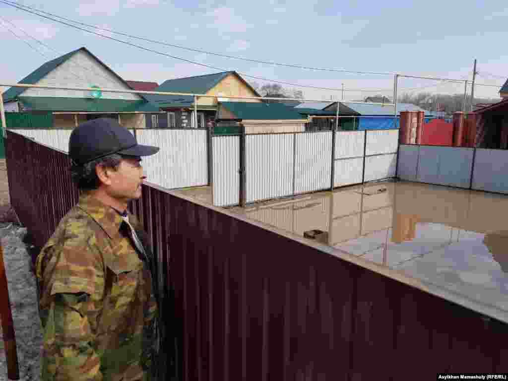 Житель села смотрит на затопленный двор.