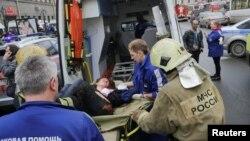 Медики и сотрудник МЧС несут раненого в карету скорой помощи у станции метро «Сенная площадь».