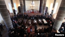 Armenia -- People surround coffins with the bodies of six murdered people during a funeral ceremony in Gyumri, January 15, 2015