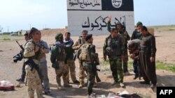 """قوات البيشمركة يقفون أمام لافتة لـ""""داعش"""" شمال الحويجة"""