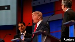 АКШ президенттигине талапкер республикачылар Скотт Уолкер (солдо), Дональд Трамп (ортодо) жана Жэб Буш (оңдо) теледебат кезде суроолорго жооп беришүүдө. Кливленд, 6-август.