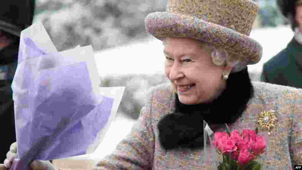 Queen Elizabeth II receives flowers after the Sunday Service at West Newton Church in West Newton on February 5, 2012, the eve of her Diamond Jubilee (60th anniversary).