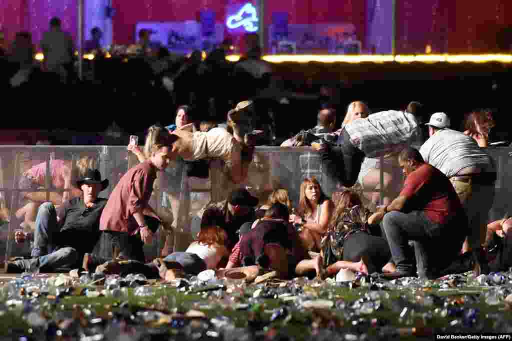 People scramble for shelter at a country music festival after a gunman fired indiscriminately into the crowd from a nearby hotel on October 1 in Las Vegas, Nevada. At least 59 people were killed and more than 500 injured in the largest mass shooting in modern U.S. history. (Getty Images/David Becker)