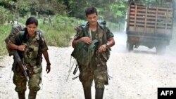 Два члена группировки ФАРК идут по дороге. Иллюстративное фото.