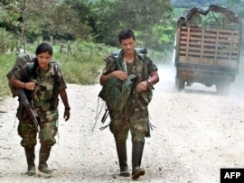 Two members of the rebel Revolutionary Armed Forces of Columbia (FARC) trek toward Los Pozos in Colombia (file photo)