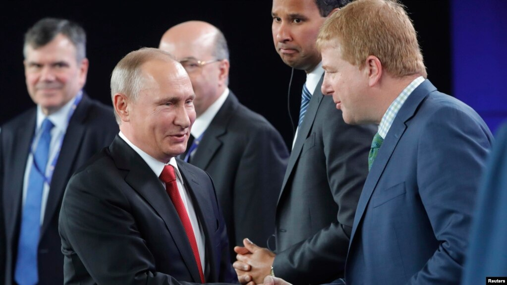 Russian President Vladimir Putin (left) shakes hands with Myron Brilliant, executive vice president and head of international affairs at the U.S. Chamber of Commerce, during a session of the St. Petersburg International Economic Forum on June 2.