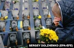 Девушка приносит цветы к мемориалу на Аллее Героев Небесной сотни в Киеве.
