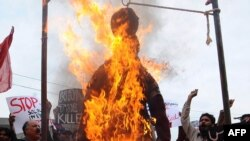 Pakistani protesters burn an effigy of CIA contractor Raymond Davis during a demonstration in Lahore on February 28.