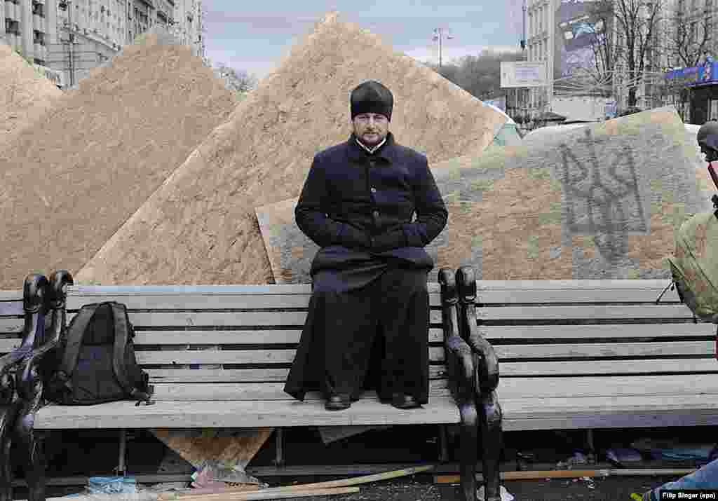 An Orthodox priest sits on a bench at Kyiv's Independence Square.